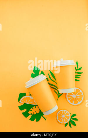 Colorful summer drink concept. Disposable paper cup on a yellow background with tropical leaves and orange slices on a bright yellow background. - Stock Photo
