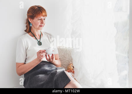 Portrait of smiling mature woman. Senior woman standing against light wall - Stock Photo