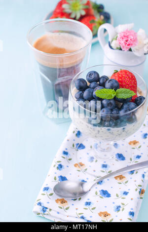 A glass of coffee and pudding chia with blueberries and strawberries for breakfast. Vegetarian healthy food. Blue background. Napkin with flowers and flowers in a vase. Bright colors. - Stock Photo