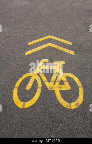 Yellow sign of a bicycle path drawn on the asphalt road. Lanes for cyclists. Cyclist on urban cycleway. Traffic signs and road safety. - Stock Photo