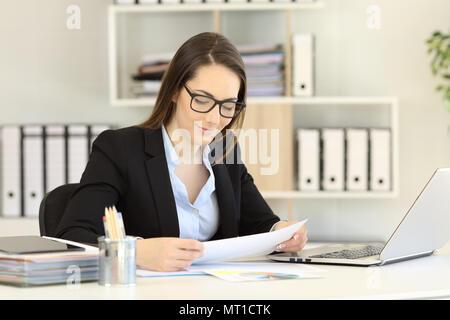 Office worker wearing eyeglasses reading a paper report on a desktop - Stock Photo