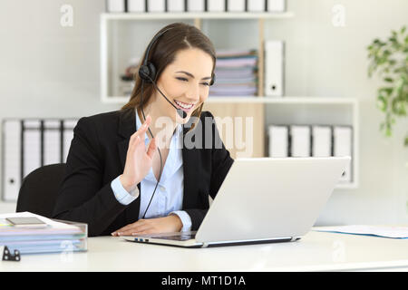 Happy telemarketer having a video conference with a laptop waving with her hand at office - Stock Photo