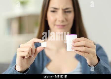Confused woman dobting between sugar and saccharine at home - Stock Photo