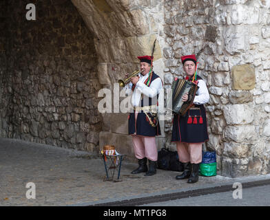 KRAKOW, POLAND - OCTOBER 28, 2015: Street musicians in national costumes from the city walls of old Krakow - Stock Photo