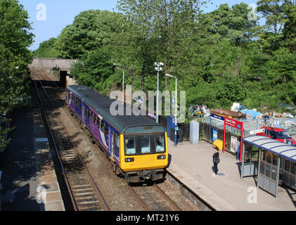 Class 142 Pacer two car dmu train in Northern livery arriving at Cherry Tree railway station, Lancashire, with a passenger waiting on the platform. - Stock Photo