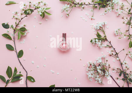 Essence of flowers on a table in a beautiful glass jar - Stock Photo
