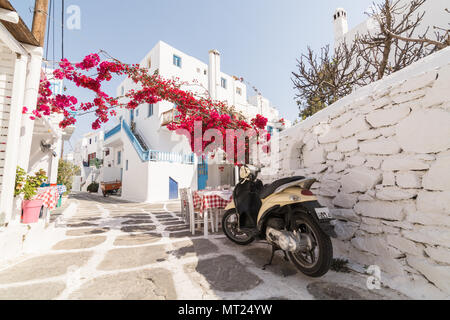 MYKONOS, GREECE - MAY 2018: Old cobbled street in Mykonos town district Little Venice, restaurant and bush in blossom. Retro scooter on foreground - Stock Photo