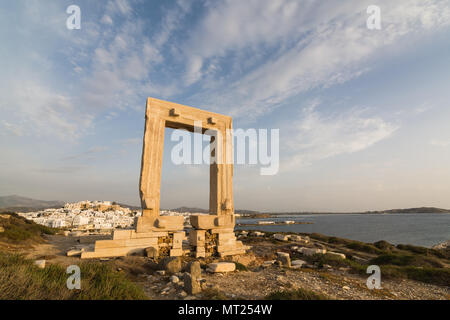 View over ruins of ancient marble doorway monument Portara at sunset in Naxos, Greece. - Stock Photo