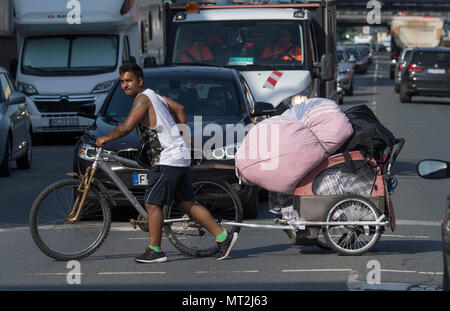 28 May 2018, Germany, Frankfurt am Main: Aman with his belongings in a bicycle trailer crosses a road after leaving a homeless camp in the Gutleutviertel district. Police began clearing the homeless camp in the morning. Photo: Boris Roessler/dpa - Stock Photo