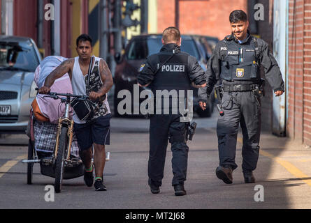 28 May 2018, Germany, Frankfurt am Main: Two police officers accompany a man across the site to a public street, as he leaves a homeless camp in the Gutleutviertel district. Police began clearing the camp in the morning. Photo: Boris Roessler/dpa - Stock Photo