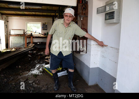 28 May 2018, Germany, Herrstein: Ulrich Schaefer points to how high the water was in his flood-damaged garage after flooding in Herrstein (Kreis Birkenfeld). Photo: Harald Tittel/dpa - Stock Photo