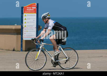 Cyclist riding Boardman bike in Blackpool, Lancashire. UK Weather.  28th May, 2018.  Bright sunny start to the day at the coast as holidaymakers and tourists enjoy the amenities and attractions on the seafront promenade. in warm sunshine. Credit:MediaWorldImages/AlamyLiveNews - Stock Photo