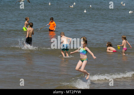 Young children playing in the sea at Blackpool, Lancashire. UK Weather.  28th May, 2018.  Bright sunny start to the day at the coast as holidaymakers and tourists enjoy the amenities and attractions on the seafront promenade. in warm sunshine. Credit:MediaWorldImages/AlamyLiveNews - Stock Photo