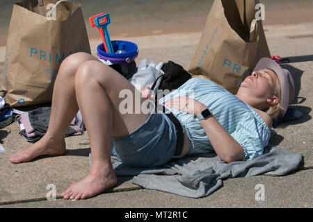 Primark shopper sunbathing at Blackpool, Lancashire. UK Weather.  28th May, 2018.  Bright sunny start to the day at the coast as holidaymakers and tourists enjoy the amenities and attractions on the seafront promenade. in warm sunshine. Credit:MediaWorldImages/AlamyLiveNews - Stock Photo