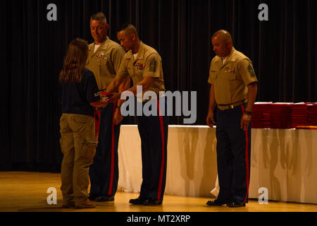 Sergeant Major Mike Lanpolsaen presents a participant from the Summer Leadership and Character Development Academy (SLCDA) with a diploma for graduation. The SLCDA is a six-day summer program designed to prepare rising high school juniors and seniors for college by introducing them to Marine Corps skills, ethics, character development, teamwork and camaraderie.