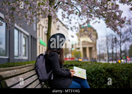 Berlin, Germany - April 3, 2017: Woman looking at the Brandenburger Tor sited on a bank - Stock Photo