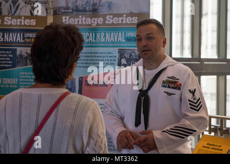 170722-N-CU914-002 ST. PAUL, Minn. (July 22, 2017) – Mass Communication Specialist 1st Class Clifford L. H. Davis, assigned to the Naval History and Heritage Command, discusses Naval heritage and history with visitors of the Minnesota Historical Society during Minneapolis/St. Paul Navy Week. Navy Week programs serve as the Navy's principal outreach effort into areas of the country without a significant Navy presence, with 195 Navy Weeks held in 71 different U.S. cities. (U.S. Navy photo by Mass Communication Specialist 2nd Class Lenny LaCrosse/Released) - Stock Photo