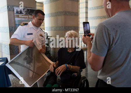 170722-N-CU914-009 ST. PAUL, Minn. (July 22, 2017) – Lt. Luke Wolf, a native of Cary, N.C., presents Army veteran, Willard Cox, with an illustration depicting the Battle of Midway while discussing Naval heritage and history with visitors of the Minnesota Historical Society during Minneapolis/St. Paul Navy Week. Navy Week programs serve as the Navy's principal outreach effort into areas of the country without a significant Navy presence, with 195 Navy Weeks held in 71 different U.S. cities. (U.S. Navy photo by Mass Communication Specialist 2nd Class Lenny LaCrosse/Released) - Stock Photo