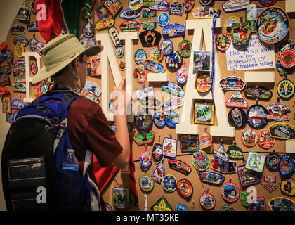 A Scout pins one of his patches to the Pin-a-Patch wall at the Summit Bechtel Reserve during the 2017 National Jamboree near Glen Jean, W.Va., July 21, 2017. The 2017 National Jamboree is being attended by 30,000 Boy Scouts, troop leaders, volunteers and professional staff members, as well as more than 15,000 visitors. Approximately 1,200 military members from the Department of Defense and the U.S. Coast Guard are providing logistical support for the event. (U.S. Army photo by Spc. Liem Huynh/22nd Mobile Public Affairs Detachment) - Stock Photo