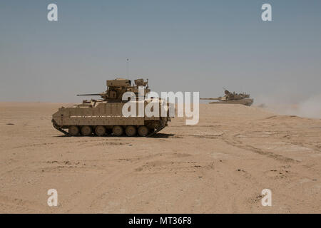 An M2A3 Bradley armored reconnaissance crew assigned to 6th Squadron, 9th Cavalry Regiment 'Saber,' 3rd Armored Brigade Combat Team, 1st Cavalry Division scans the terrain for 'enemy' targets while an M1A2 Abrams Main Battle Tank crew provides direct fire support for the reconnaissance element during Hunter-Killer training at the Kuwait Multipurpose Range Complex June 7. Saber Squadron is developing Hunter-Killer as a concept, teaming Bradleys up with tanks for increased firepower and speed in the reconnaissance mission. (U.S. Army photo by Staff Sgt. Leah R. Kilpatrick/released) - Stock Photo