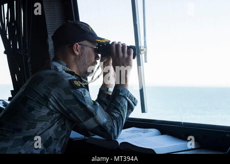 170727-N-ZL062-016 MORETON BAY (July 27, 2017) Royal Australian Navy Cmdr. Brendan O'Hara, from Carwoola, New South Wales, Australia, observes ships through binoculars in the pilot house of the amphibious transport dock USS Green Bay (LPD 20) during a sea and anchor detail. Green Bay, part of the Bonhomme Richard Expeditionary Strike Group, is operating in the Indo-Asia-Pacific region to enhance partnerships and be a ready-response force for any type of contingency. (U.S. Navy photo by Mass Communication Specialist 3rd Class Sarah Myers/Released) - Stock Photo