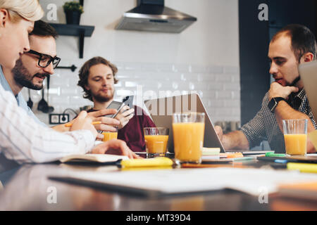 Group of young manager discussing during a meeting. Teamwork on a new startup. Team of businessmen working with electronic gadgets - Stock Photo