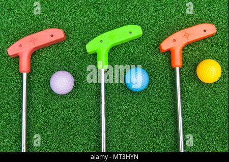 Three colorful rubber golf clubs with balls for miniature golf - Stock Photo
