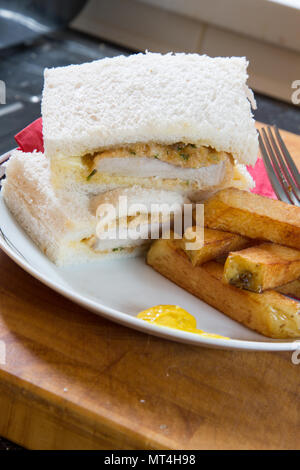 A snack/lunch of fried breaded Pork steak sandwich with white sliced bread and potato chips/fries - Stock Photo