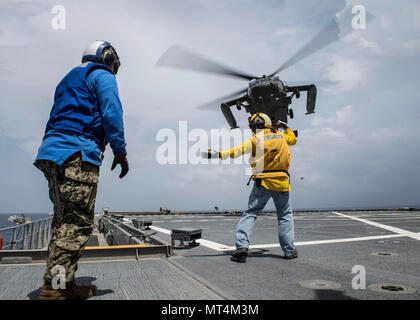 170726-N-YM856-174 CARIBBEAN SEA (July 26, 2017) Landing Signalman Jimmy Conner, right, a civilian mariner assigned to Military Sealift Command, performs helicopter deck landing qualifications aboard expeditionary fast transport USNS Spearhead (T-EPF-1) during Southern Partnership Station-Expeditionary Fast Transport 2017. SPS-EPF 17 is a U.S. Navy deployment executed by U.S. Naval Forces Southern Command/U.S. 4th Fleet, focused on subject matter expert exchanges with partner nation militaries and security forces in Central and South America. (U.S. Navy Combat Camera photo by Mass Communicatio - Stock Photo