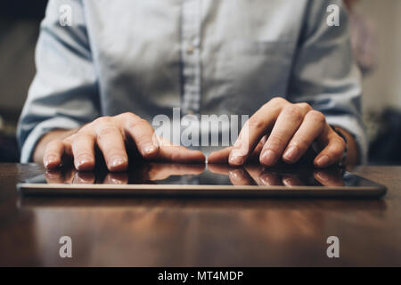 Close up view on male hands typing on screen modern tablet. Computer touch pad on wooden table - Stock Photo