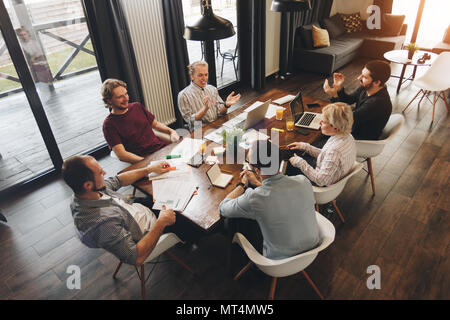 Coworking meeting. Group business people sits around table and working on laptops and tablet. Startup team discussing new project together - Stock Photo