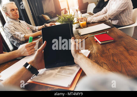 POV view of male hands holding computer tablet. Group of young coworkers sits around table, working together and discuss project. Creative managers me - Stock Photo