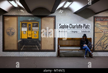 Berlin, Germany - April 4, 2017: Girl/Woman sitting on a bench at Sophie Charlotte Platz subway station in Berlin - Stock Photo