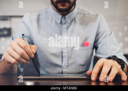 Bearded businessman working on tablet with stylus. Businessman hands working on laptop. Concept digital touch pad on wooden table - Stock Photo