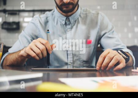 Bearded man using tablet for video conversation in modern office. Concept of young business people working at home. Bearded man use generic design lap - Stock Photo