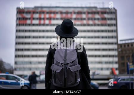 Berlin, Germany - April 4, 2017: Girl/Woman looking at 'Stop Wars' Graffiti on a building in Berlin Alexanderplatz - Stock Photo