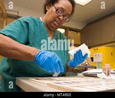Pamela Baker, 88th Medical Operations Squadron cytology technician, places finished cytology slides to a flat surface for microscopic analysis by a pathologist inside the cytology lab at Wright-Patterson Air Force Base Medical Center, June 26, 2017. A pathologist orders a surgical pathology specimen when a core biopsy has been obtained. (U.S. Air Force photo by Michelle Gigante) - Stock Photo