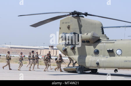 TAJI MILITARY COMPLEX, Iraq – Members of the Iraqi security force load onto a CH-47F Chinook helicopter fielded by the 29th Combat Aviation Brigade at Camp Taji Military Complex, Iraq, July 19,2017. The ISF trained with their U.S. counterparts in the 82nd Airborne Division's Task Force Red Falcon and the 29th CAB on security procedures involving aircraft and met to schedule future partnership events. This training is part of the overall Combined Joint Task Force – Operation Inherent Resolve building partner capacity mission by training and improving the capability of partnered forces fighting  - Stock Photo