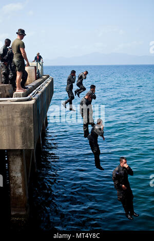 Honduran marines jump into the waters of the Caribbean Sea during a course on basic water survival skills taught by U.S. Marine Sgt. Travis R. DiPiazza, an infantry trainer with the Honduras Detachment, Ground Combat Element, Special Purpose Marine Air-Ground Task Force - Southern Command in Trujillo, Honduras, July 26, 2017. The training was part of a basic infantry skills course for Honduran marines. The Marines and sailors of SPMAGTF-SC are deployed to Central America from June to November 2017 to conduct security cooperation training and engineering projects with their counterparts in Beli - Stock Photo