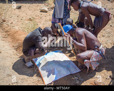 Opuwo, Namibia - July 25, 2015: Group of Himba men and boys leaning over and looking at map of Namibia - Stock Photo
