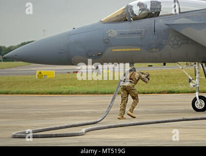 U.S. Air Force Airman 1st Class Sequan Gill, 100th Logistics Readiness Squadron forward arming and refueling point technician runs out a fuel hose to an F-15C Eagle from RAF Lakenheath July 26, 2017, on RAF Mildenhall, England. A FARP allows for aircraft to be able to rearm and refuel at an austere location and return to the mission without having to land at an actual base. (U.S. Air Force photo by Airman 1st Class Luke Milano) - Stock Photo