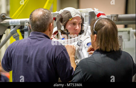 Canadian Space Agency astronaut David Saint Jacques helps Astronaut Col. Tyler N. 'Nick' Hague prepare to be lowered into a pool with a mockup of the International Space Station (ISS) for Extravehicular Activity (EVA) training at the Johnson Space Flight Center's Neutral Buoyancy Laboratory (NBL) in Houston, Tex., Apr. 27, 2017. During  training at NBL, Hague wears a spacesuit to simulate the near weightless environment he will encounter while performing EVAs, or spacewalks, while serving as a flight engineer on Expedition 54/55 aboard ISS in 2018-2019.  (U.S. Air Force photo by J.M. Eddins Jr - Stock Photo