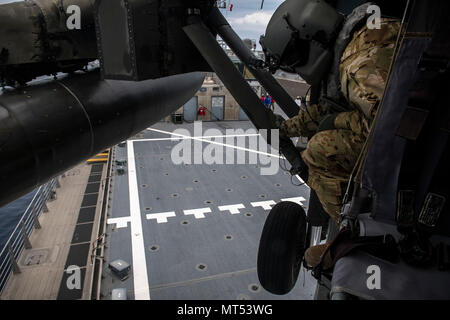 U.S. Army SGT Andrew Corbin, Standardization Instructor, 1-228th Aviation Regiment Charlie Company helps guide the UH-60 Blackhawk as it conducts deck landing qualification aboard the USNS Spearhead off the coast of Honduras in the Caribbean Sea, July 27, 2017. The 1-228th C-Company deck landing qualification consisted of classroom instruction and 5 landings with an Instructor Pilot. Once qualified each Pilot will need to maintain their currency on a scheduled timeline. (U.S. Air National Guard photo by Master Sgt. Scott Thompson/released) - Stock Photo