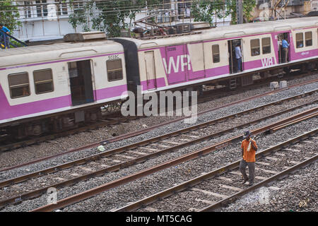Railway worker walking on the tracks of the local train in Mumbai as a  train passes him by. - Stock Photo