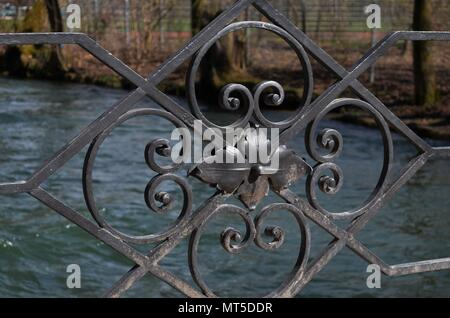 close-up of the black iron ornaments of a bridge's handrail with river flowing in the background - Stock Photo