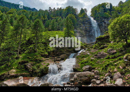 Big Waterfall in the forest, spring season near the little ancient village of Sonogno in Switzerland - Stock Photo