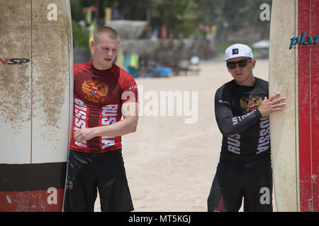 Mirissa/Sri Lanka - April 4, 2018: Two sports men stand on the beach with surfboards. - Stock Photo