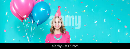 Gorgeous birthday girl in party outfit holding colourful balloons. Attractive trendy teenager celebrating birthday. Party and flying confetti. - Stock Photo