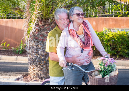 senior couple in love leisure outdoor together on a bike vintage style smiling and having fun under the sun of vacation. alternative way to be retired - Stock Photo