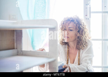 beautiful caucasian woman diy do it herself yourself a furniture renewed at home with the window light. concentrated expression for middle age lady pa - Stock Photo
